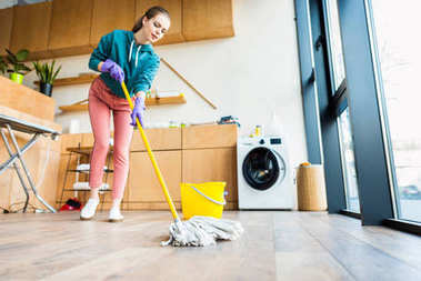 low angle view of young woman cleaning home with mop