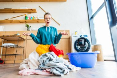 shocked young woman looking at laundry
