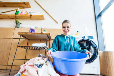 young woman holding plastic basin and smiling at camera while kneeling near clothes and washing machine