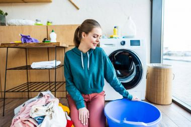 smiling young woman looking at plastic basin while kneeling near clothes and washing machine