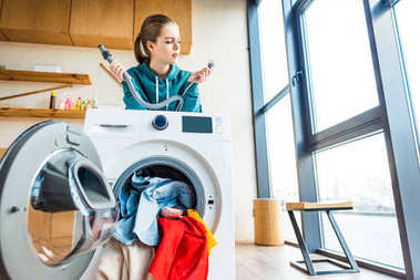 young woman leaning at broken washing machine