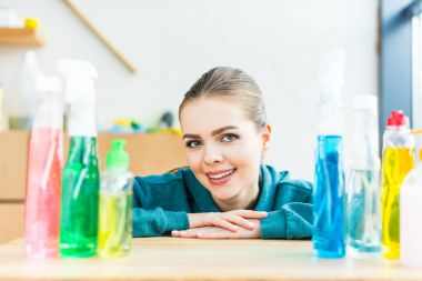 young woman smiling at camera while sitting at table with plastic bottles with cleaning products