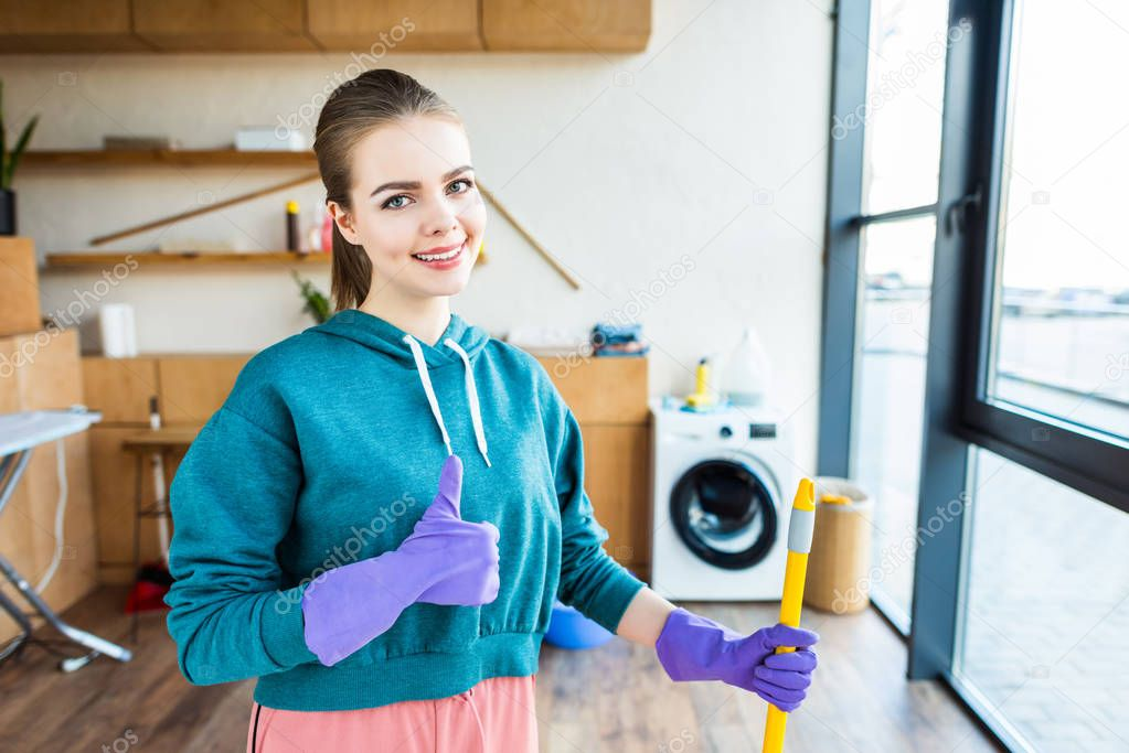 smiling young woman cleaning house with mop and showing thumb up