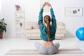 zadní pohled na dívka sedí v lotosové pozici a dělá jógu doma