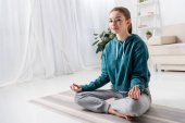 Photo beautiful girl sitting in lotus position on yoga mat and looking at camera at home