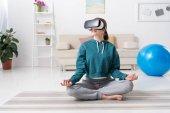 dívka sedí v lotosové pozici s doma soupravu pro virtuální realitu