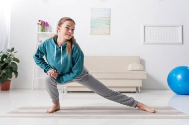 girl stretching legs on yoga mat and looking at camera at home