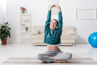 smiling girl sitting in lotus position and doing yoga at home
