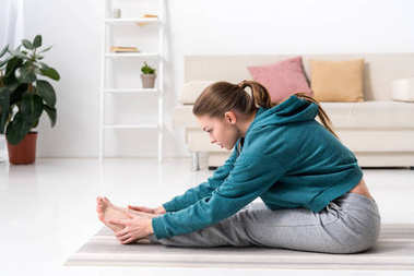 side view of girl stretching in sportswear at home