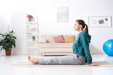 side view of girl sitting on yoga mat at home