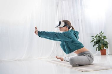 side view of girl stretching with virtual reality headset on yoga mat at home
