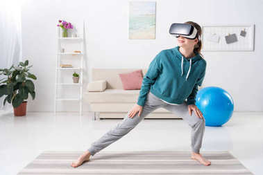 girl stretching legs with virtual reality headset on yoga mat at home
