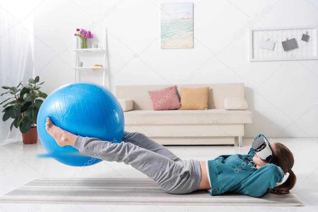 girl exercising with fitness ball and in virtual reality headset at home