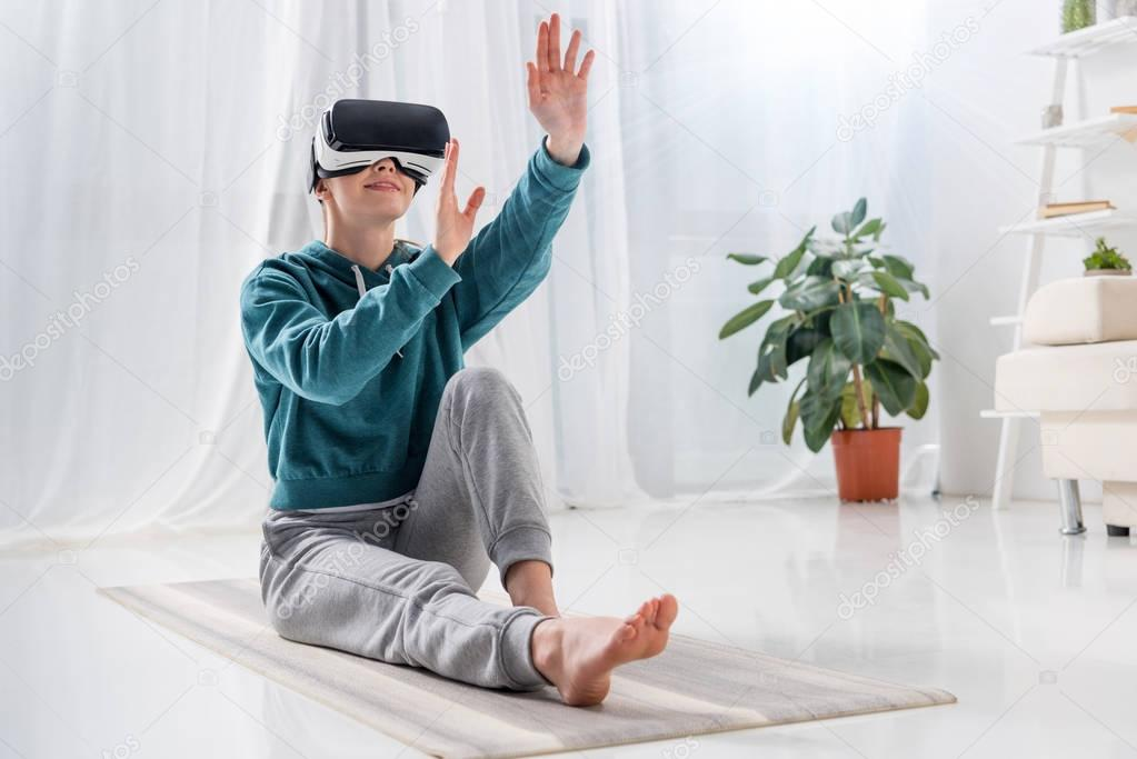 girl sitting on yoga mat with virtual reality headset and touching something at home