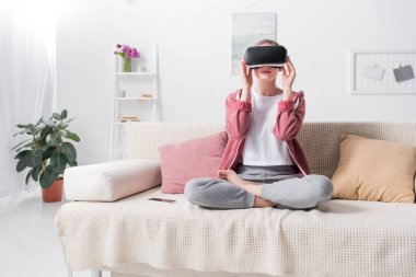girl sitting in lotus position with virtual reality headset on sofa at home