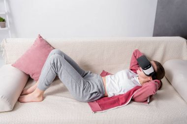 high angle view of girl doing sits up with virtual reality headset on sofa at home