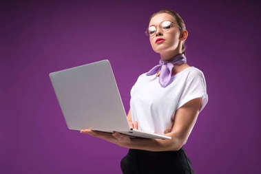 girl holding laptop and looking at camera isolated on purple