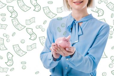 cropped shot of woman holding piggy bank in hands, falling dollar banknotes with coins symbols isolated on white