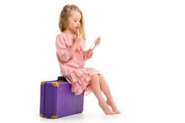 Side view of stylish child sitting on suitcase and doing makeup by lipstick isolated on white stock vector