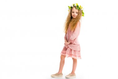 Child in pink dress wearing wreath band from flowers isolated on white