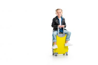 Little tourist with pigtails wearing leather jacket and sitting on wheel suitcase isolated on white
