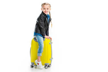 Smiling little tourist sitting on yellow wheel suitcase isolated on white