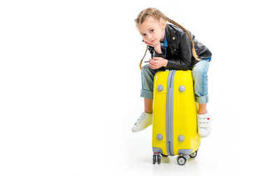 Little kid with pigtails holding hand on chin and sitting on wheel suitcase isolated on white