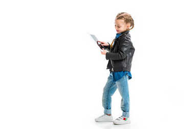 Side view of standing little child using digital device isolated on white