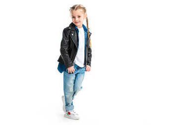 Little stylish kid wearing black leather jacket standing with fingers in pockets isolated on white