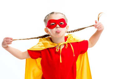 Little supergirl in yellow cape and red mask for eyes showing tongue and holding pigtails isolated on white