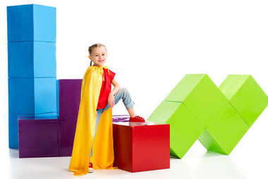Little smiling supergirl wearing yellow cape and standing on cube isolated on white