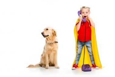 Shocked little supergirl wearing yellow cape and talking on phone with standing dog beside isolated on white