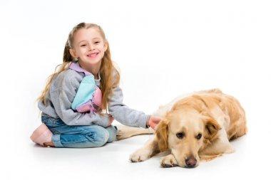 Smiling child touching beige dog isolated on white