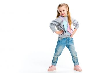 Stylish child standing with arms on thighs isolated on white