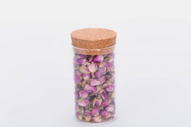 close-up view of dry pink rose buds in glass jar isolated on white