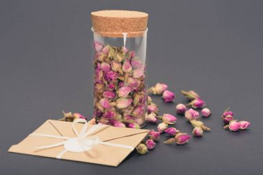 dry pink rose buds in glass jar and envelope on grey