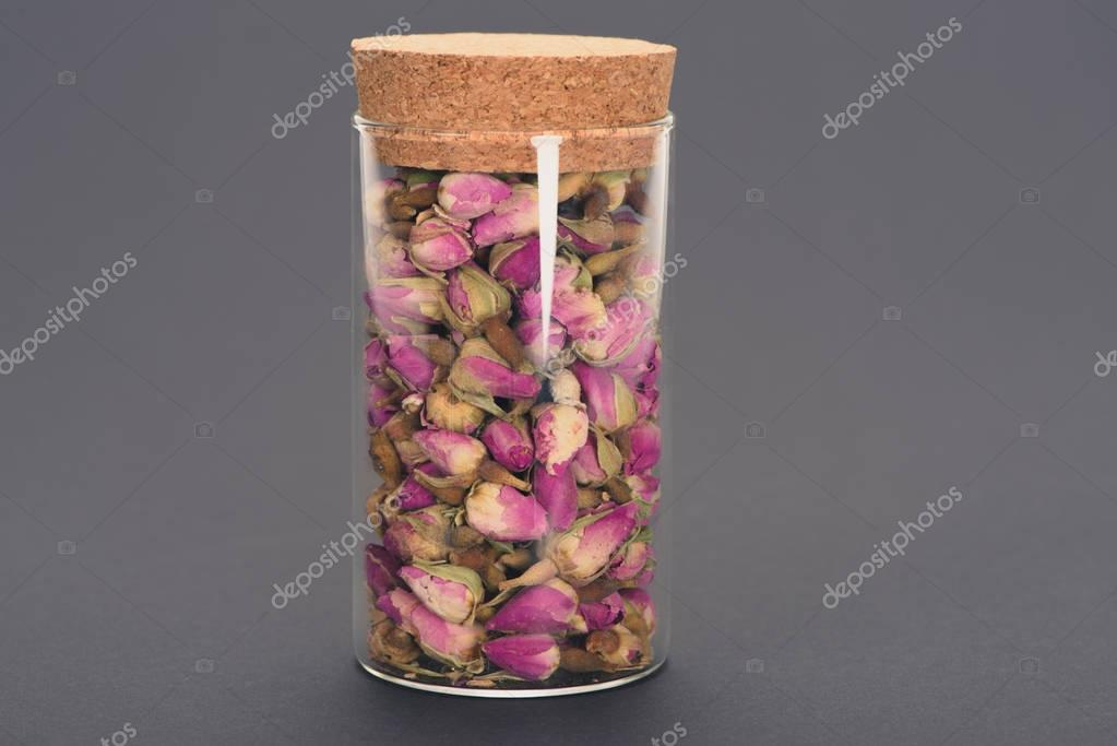 close close-up view of beautiful dry rose buds in glass jar isolated on grey