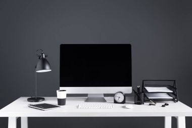 desktop computer with blank screen, clock and office supplies at workplace