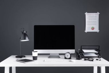 desktop computer with blank screen, business chart, clock and office supplies at workplace
