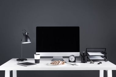 desktop computer with blank screen, food on plate and office supplies at workplace