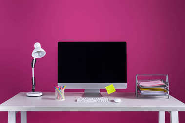desktop computer with blank screen, office supplies and lamp on table on pink