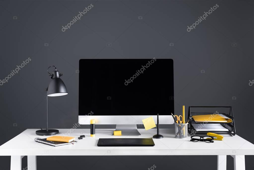 desktop computer with blank screen, graphics tablet and office supplies at workplace