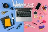 Fotografie pohled shora laptop, smartphone, nápis pracoviště a kosmetiky s kancelářské potřeby rozdělen na mužské a ženské pracovišti