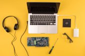 Photo top view of laptop with headphones, eyeglasses and motherboard on yellow
