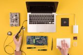 Photo partial top view of person holding eyeglasses and fixing laptop on yellow