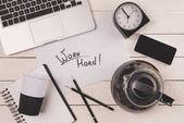laptop, kávové konvice, pohárek, hodiny, smartphone a nápis tvrdě pracovat na pracovišti