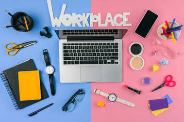 top view of laptop, smartphone, inscription workplace and cosmetics with office supplies divided at male and female workplace