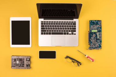 top view of digital devices with black screens and motherboard and hardware on yellow