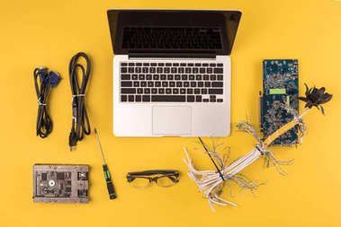 top view of laptop with blank screen, wires, motherboard and hardware on yellow