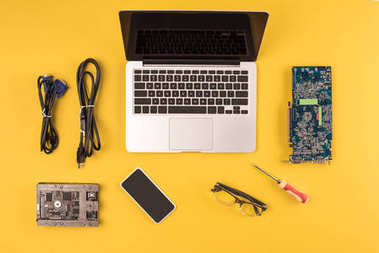 top view of laptop, smartphone, eyeglasses and wires on yellow